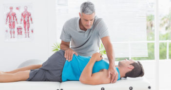 44808065 - doctor stretching a young man back in medical office