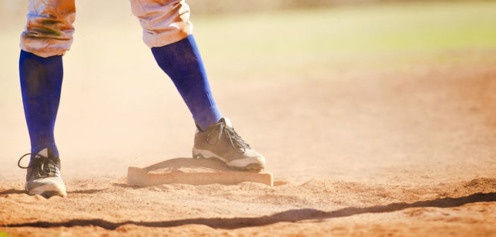 33406638 - baseball player wearing blue socks standing on a baseball base.